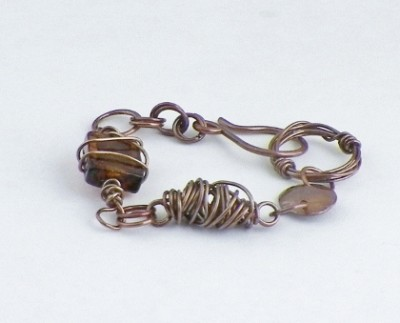 Disk and wire wrapped glass bracelet